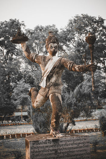 Woman statue against trees and plants