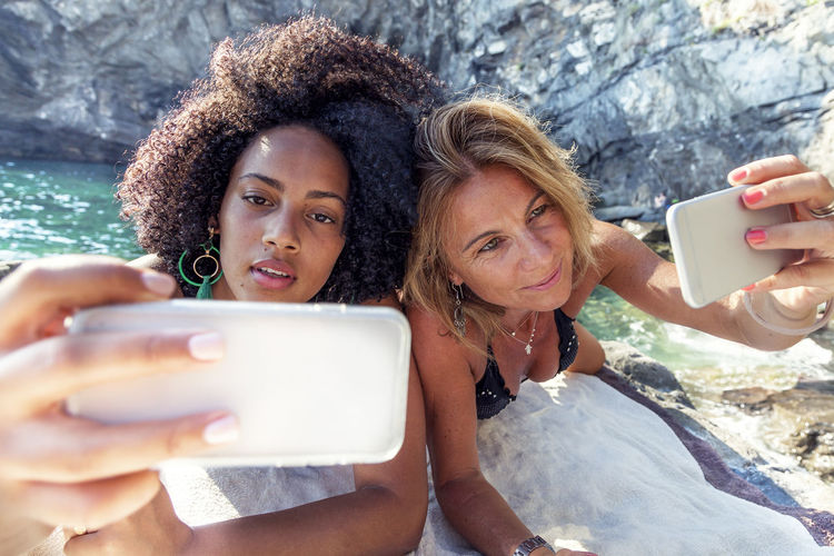 Smiling Two Women Taking Selfie While Lying On Rock Formation At Sea