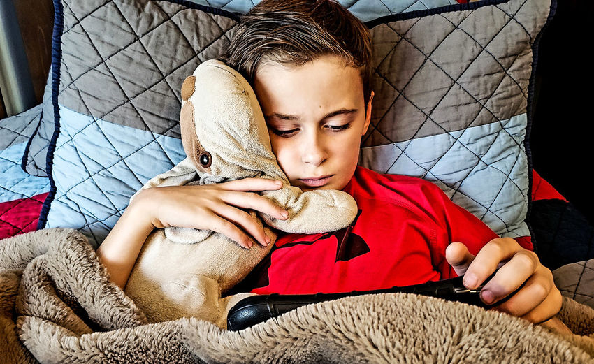little boy with his puppy surfing the web with his mobile device. Kids Fun Cozy Moments Cozy Blanket Cute Little Boy Kid Ipad Kid Learning Learning Watching Video Watching A Movie Kids Fun In Bed Studying EyeEmNewHere Human Hand Child Childhood Close-up Stuffed Toy Toy Animal Animal Representation Toy Thoughtful