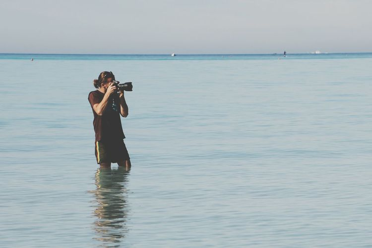 Photographer photographing through dslr while standing amidst sea