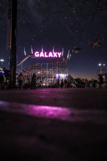 GALAXY Amusement Park Amusement Park Ride Architecture Arts Culture And Entertainment Building Exterior Built Structure City Group Of People Illuminated Incidental People Leisure Activity Lighting Equipment Long Exposure Nature Night Outdoors Real People Sky Street