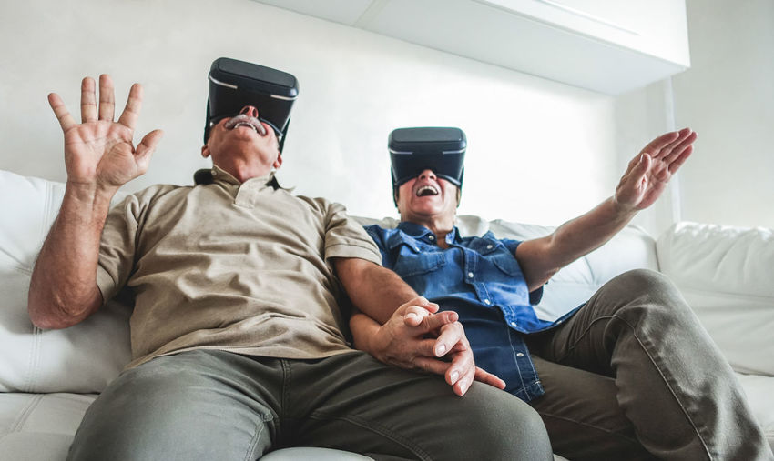 Low angle view of senior couple looking through virtual reality simulators while sitting on sofa at home