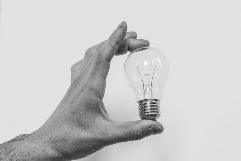 hand he is holding up a light bulb Adult Adults Only Close-up Day Holding Human Body Part Human Finger Human Hand Index Finger Indoors  One Person People White Background
