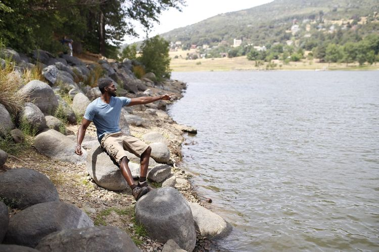 Man surfing on rock by river
