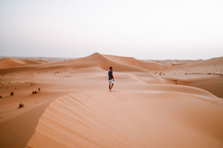 Man standing at desert against clear sky