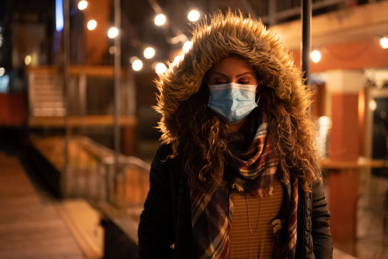 Portrait of woman wearing a mask at night in the city in 2020