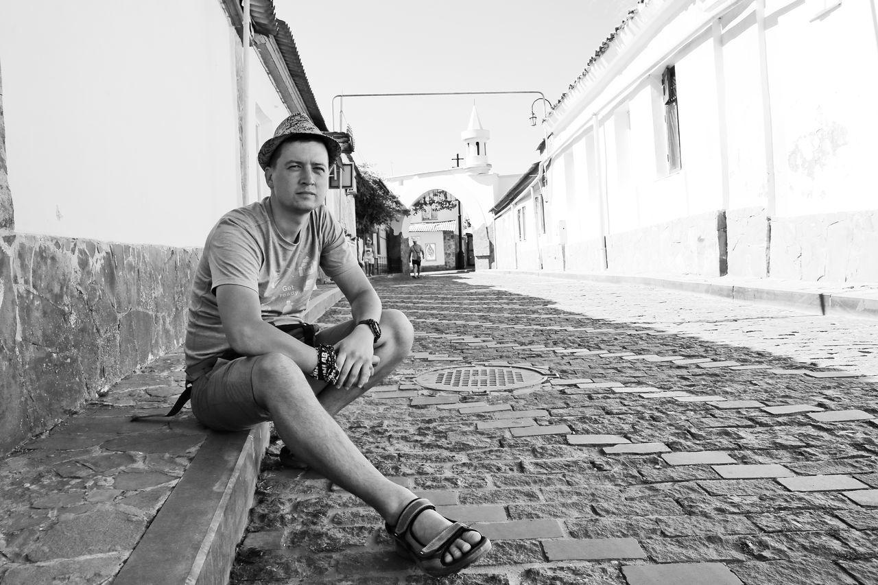 Man Sitting On Street Amidst Buildings
