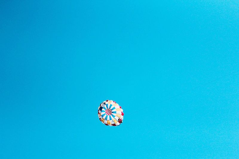 Low angle view of parachute flying against clear sky