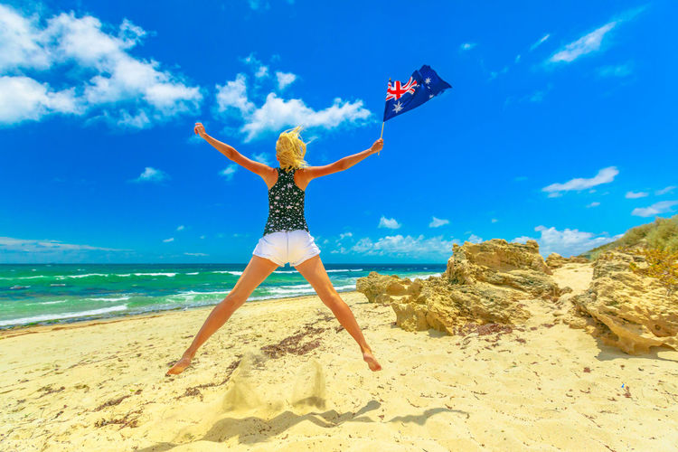 Rear view full length of woman holding australian flag jumping at beach