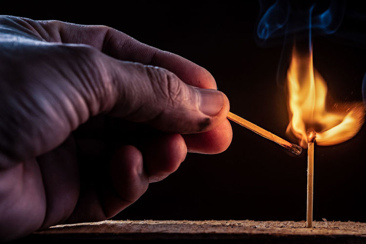 Midsection of person holding burning candle