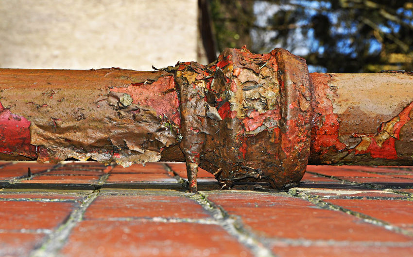 Close-up of rusty pipe attached to wall