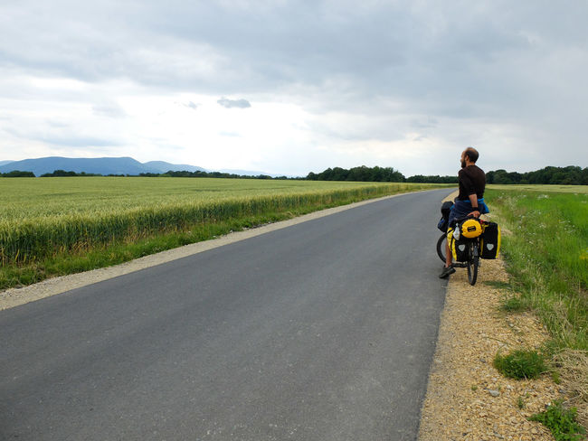Adult Beauty In Nature Bike Packing Bike Touring Cloud - Sky Day Full Length Grass Helmet Landscape Leisure Activity Men Nature Outdoors People Real People Rear View Riding Road Scenics Sky The Way Forward Transportation Two People