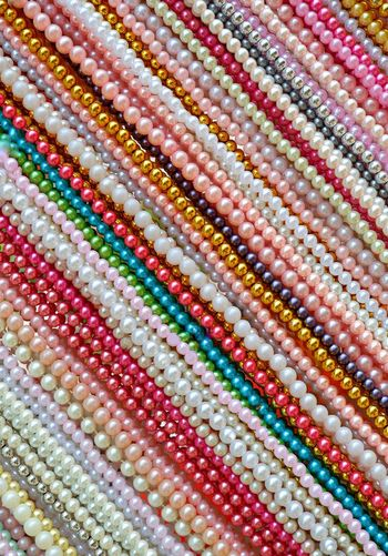 Diagonal lines pattern of multicolored beads necklace accessories background in handicrafts fashionable for women, vertical frame Lines Handicrafts Fashionable String Bright Plastic Circular Shape Decoration Art Background Multicolored Colorful Vertical Frame Diagonal Multi Colored Backgrounds Full Frame Textured  Variation Pattern Retail  Close-up Display Collection Bead Raw Retail Display For Sale Various