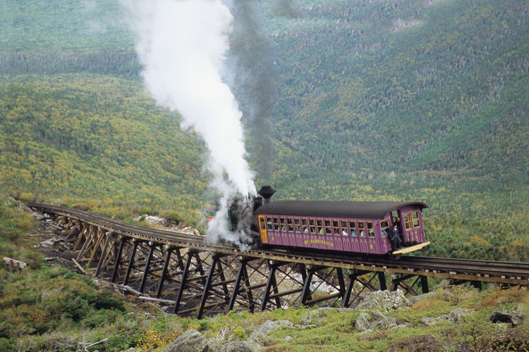 Steam locomotive pushing up Coach to the summit of of Mount Washington at the famous Jacobs Ladder bridge Bretton Woods Resort Mount Washington Cog Railway Narrow Gauge Railway New Hampshire, USA United States Air Pollution Day Environment Land Landscape Mode Of Transportation Motion Mountain Nature No People on the move Outdoors Plant Pollution Public Transportation Rail Transportation Smoke - Physical Structure Steam Train Train Train - Vehicle Transportation Tree