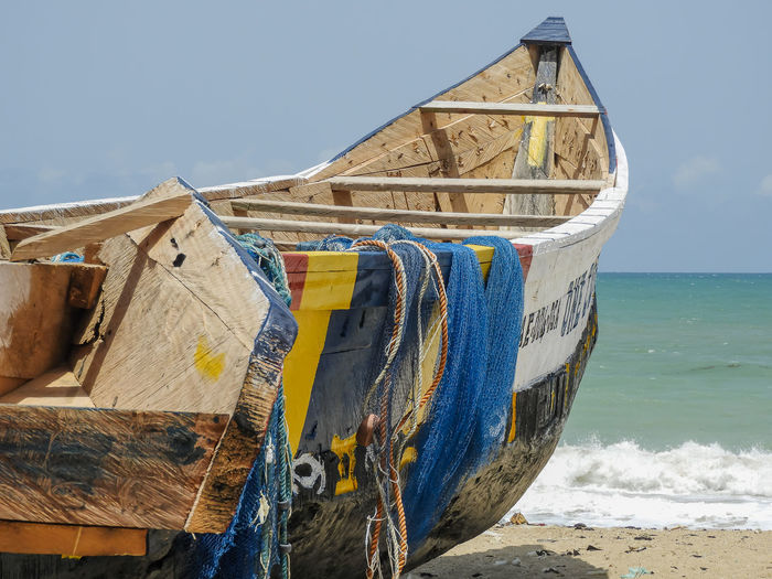 Fishing boat on beach against clear sky