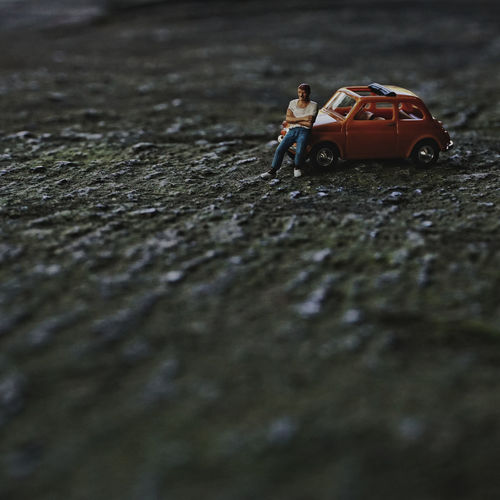 Close-up of toy car with figurine on floor