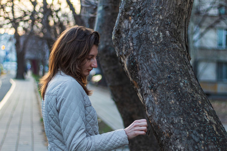 The woman and the tree Face Street Beautiful Woman Street Photography Walk City Girl Urban Long Hair Beautiful Warm Clothes Woman White Jacket Outdoors Outside Adult Woman Poertrait Tree Young Adult Real People One Person Leisure Activity Lifestyles Women Side View Trunk Focus On Foreground Plant Tree Trunk Adult Nature Casual Clothing Day Young Women Standing Hairstyle Warm Clothing Contemplation Teenager The Portraitist - 2019 EyeEm Awards