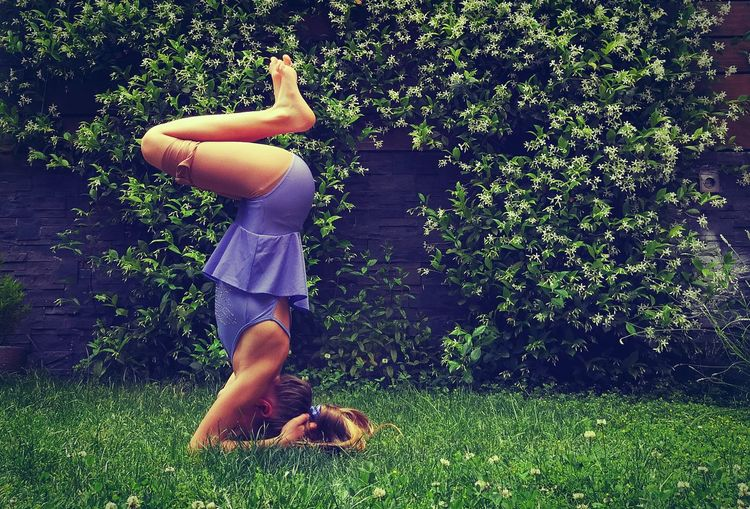 Full length side view of girl practicing headstand on grass at back yard