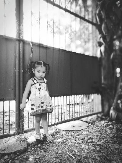 Cute girl standing against gate