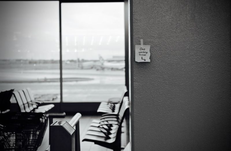 Adhesive note stuck on wall in airport building