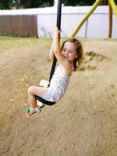 Full length of cute girl sitting while zip lining at playground