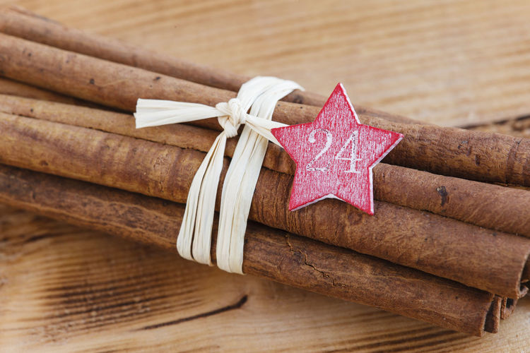 Bundle of cinnamon sticks with star shape tag on table