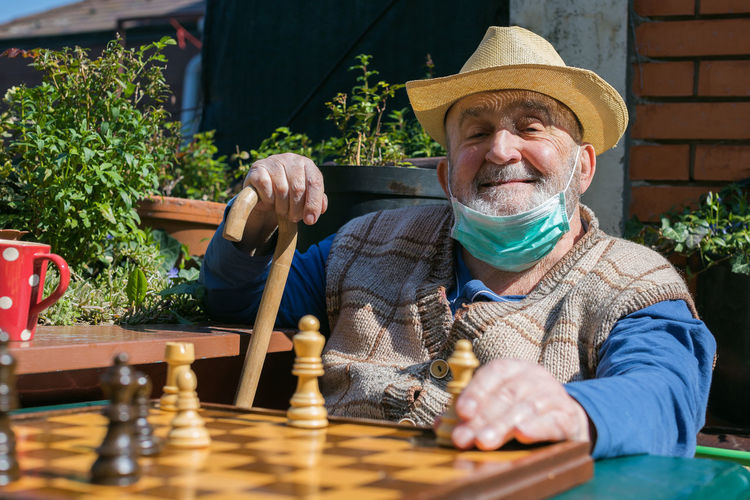 Portrait of senior man wearing mask playing chess while sitting outdoors