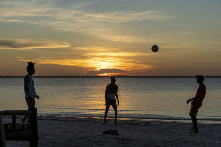 Men playing with ball on beach against sky during sunset