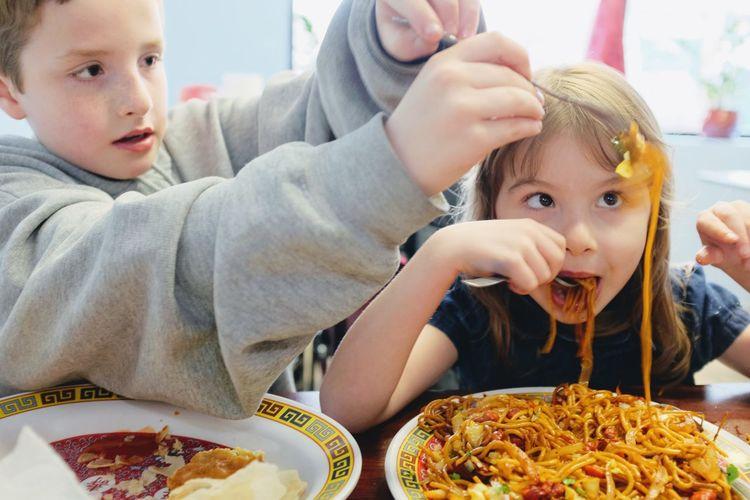 Cute siblings eating food at restaurant