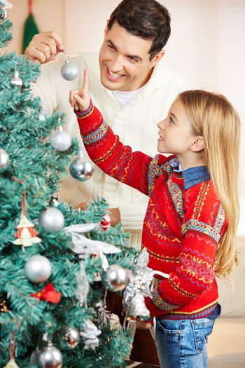 Smiling father and daughter decorating christmas tree at home