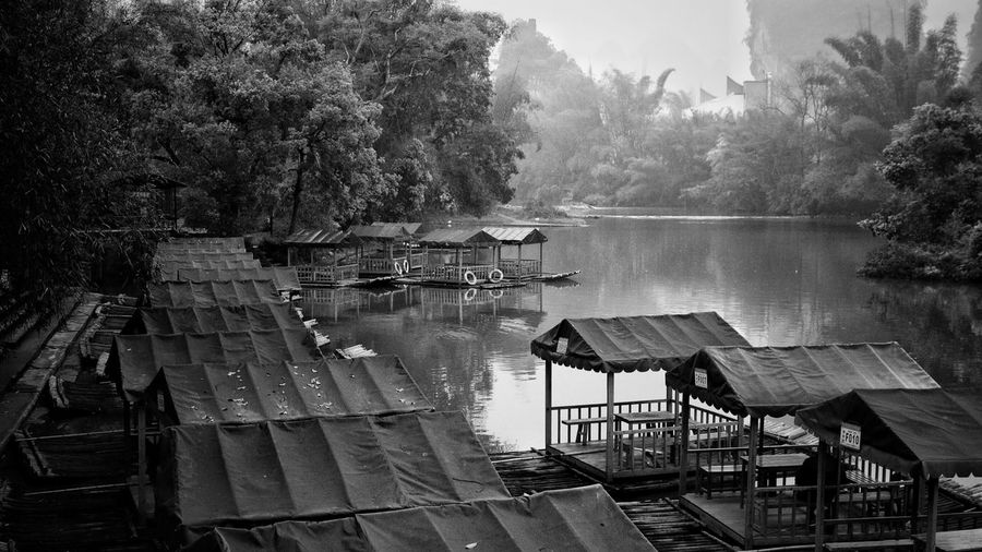 High angle view of houseboats moored in river during foggy weather