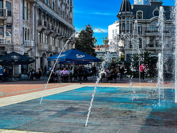 Fountain by swimming pool against buildings in city