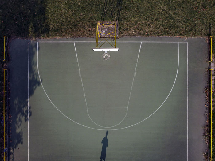 Drone view of a basketball court with player shadow in pavia, italy