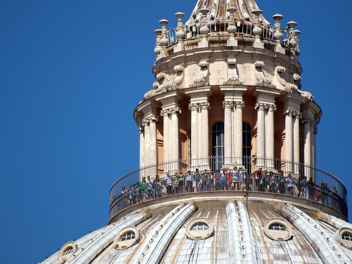 Low angle view of tourist standing on st peters basilica dome against clear blue sky