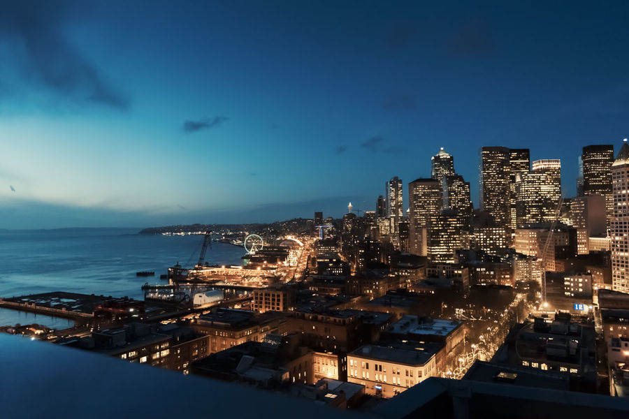 Aerial view of downtown Seattle Washington at dusk with waterfront. Bird Eye View Aerial Architecture Blue Building Exterior Built Structure City Cityscape Dawn Dusk Flying Glowing Homeless Population Housing Crisis Illuminated No People Outdoors Real Estate Sea Sky Travel Destinations