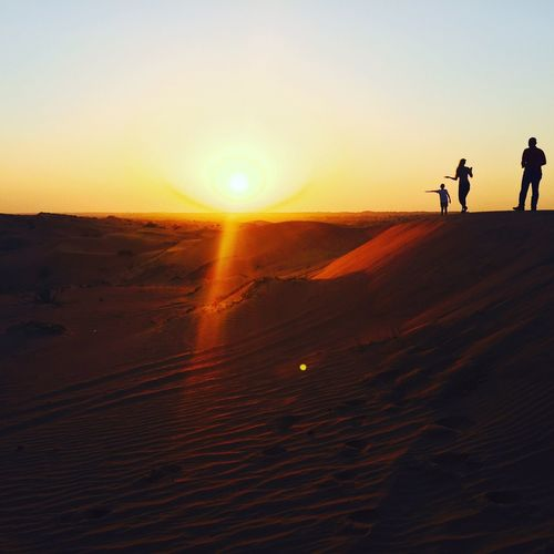 Silhouette people walking on desert against clear sky during sunset