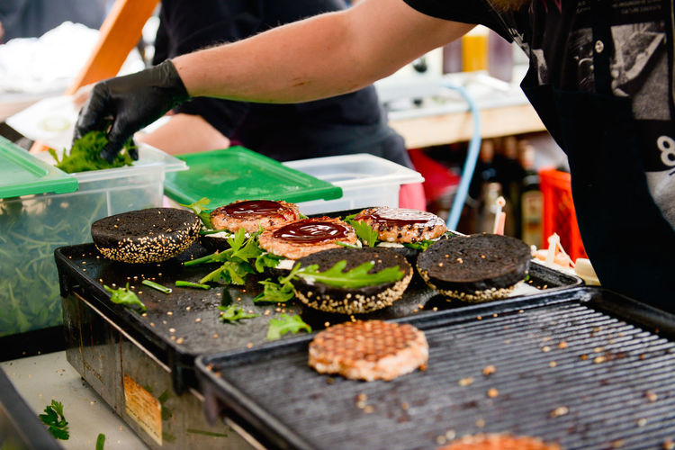 Burger Burgers Calories Cooking Cropped Eating Food Freshness Holding Indulgence Leisure Activity Lifestyles Market Market Stall Meat Part Of Person Preparation  Preparing Preparing Burgers Preparing Food Ready-to-eat Retail  Unhealthy Eating Street Food Worldwide