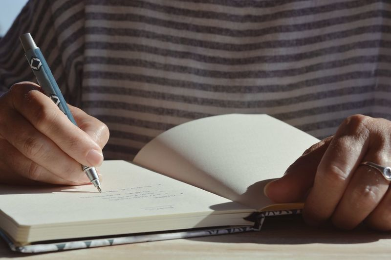 Midsection of man reading book on table