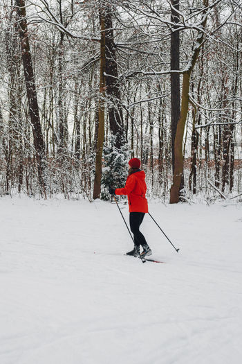 Full length rear view of person walking on snow covered field