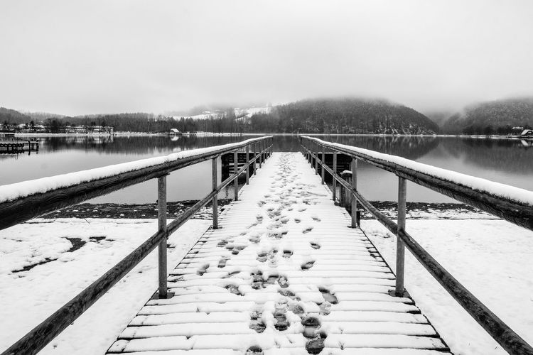 Jetty Eyem Premium Selected Black & White Nature Symetry Tranquility Beauty In Nature Bridge Cold Temperature Day Foggy Footbridge Lake Lakeside Beauty No People Outdoor Railing Scenics Sky Snow Covered The Way Forward Tree Water