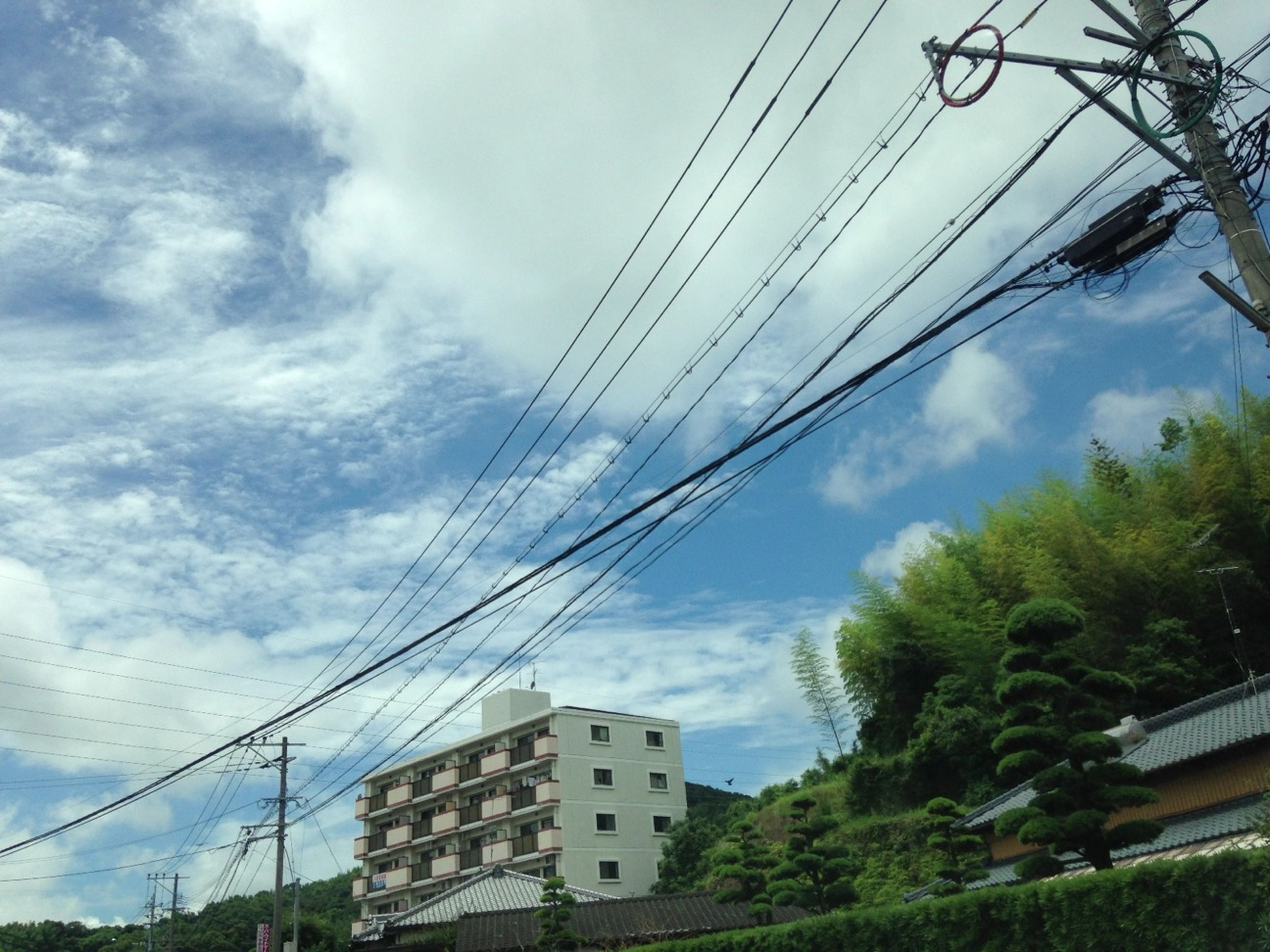 power line, electricity pylon, cable, power supply, electricity, sky, building exterior, low angle view, architecture, connection, built structure, fuel and power generation, cloud - sky, power cable, house, tree, technology, cloud, cloudy, residential structure