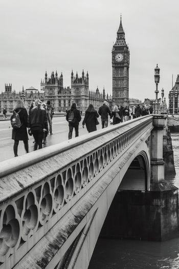 People walking on westminster bridge by big ben against sky in city