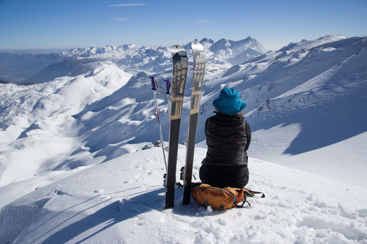 Woman with snowboards sitting on snowcapped mountain against sky