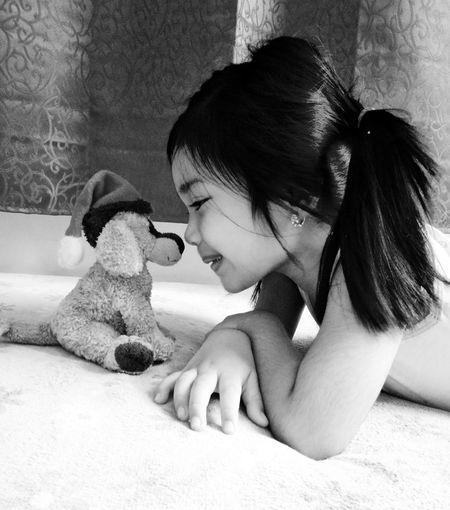 Close-Up Of Girl Playing With Toy Animal On Floor