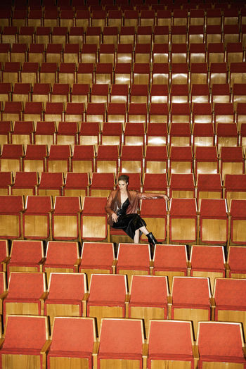 Woman sitting on chair in auditorium