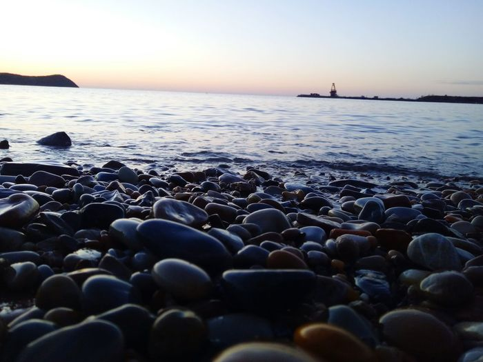 Beach Sea Sunset Horizon Over Water Pebble Silhouette Beauty In Nature Wave Sky Beauty Sun Nature Water's Edge Outdoors Blue Travel Destinations Vacations Water No People Pebble Beach