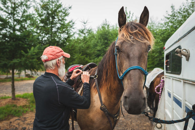 Man tying saddle on horse by van