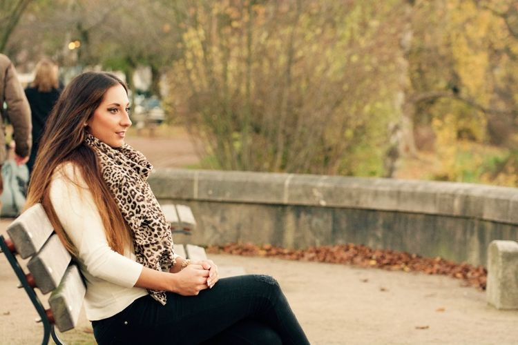 Beautiful Woman Sitting On Bench Against Trees In Park