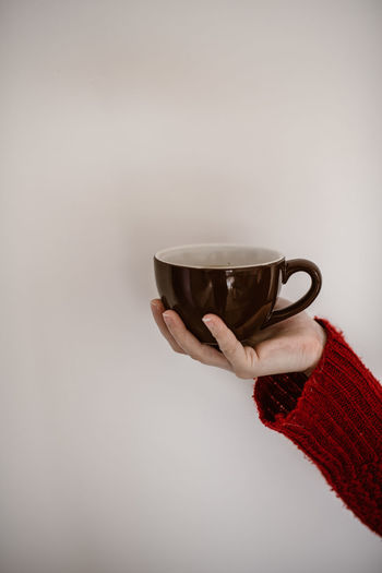 Woman holding coffee cup against white background