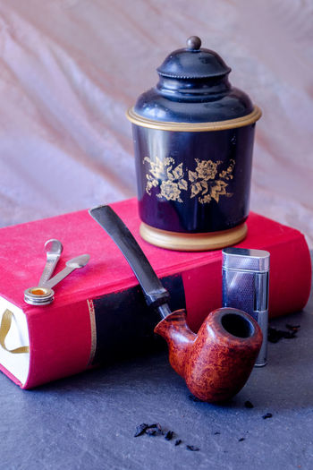 a beautiful wood pipe rests against a favorite book with a humidor of tobacco and a silver lighter Vertical Still Life Antique Classic Red Relaxing Retro Smoking Addiction Addictions  Book Collection Habit Humidor  Lifestyles Lighter Pipe Pipe - Tube Smoker Smoking Pipe Smoking Pipes Tobacco Product Tools Vintage Wood - Material